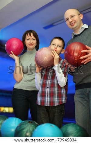 Mother, father and son, stand alongside and hold balls for bowling, focus on father and son - stock photo
