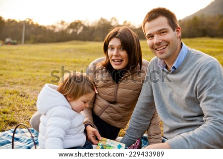 Mother Father and their little baby having happy times together in autumn outdoor in the green wood and grass