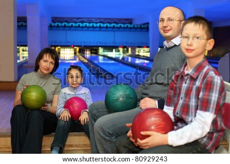 Mother, father and two children, sit in club and hold balls for bowling on knees, focus on  girl and mother - stock photo