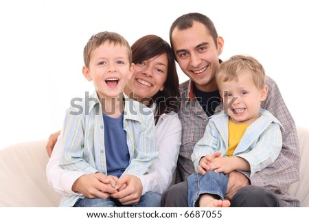 mother father and two sons on the sofa - happy family - stock photo