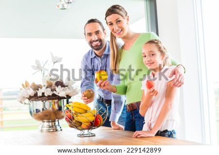 Mother, father, child picking fresh fruits for healthy living in home kitchen - stock photo