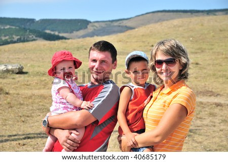 mother, father, son and daughter are outdoors, they are happy