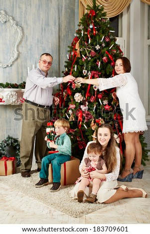 Mother, father, two girls and boy decorate christmas tree