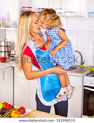 Mother  feed happy child at kitchen . - stock photo