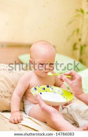 Mother feed her son at home - stock photo