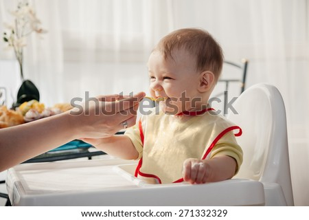 Mother Feeding Adorable Baby Boy  - stock photo