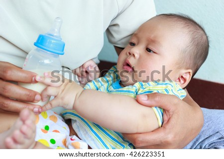 Mother feeding baby, baby infant eating milk from bottle - stock photo