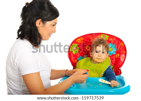 Mother feeding baby boy isolated on white background