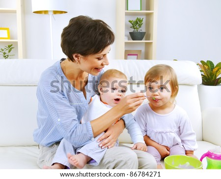 Mother feeding baby food to babies - stock photo