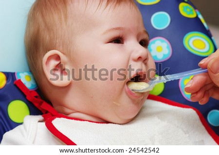 Mother feeding baby food to baby - stock photo