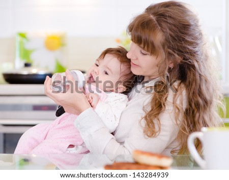 Mother feeding baby with feeding bottle in kitchen - stock photo