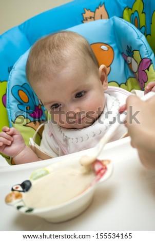 Mother feeding caucasian baby - stock photo