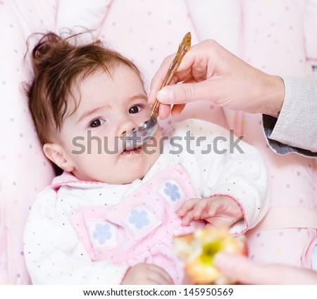 mother feeding her baby apple puree  - stock photo