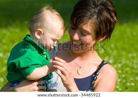 mother feeding her baby boy a strawberry - stock photo