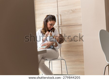 Mother feeding her baby boy.They sitting on chair in bright room. - stock photo