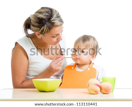mother feeding her baby girl by spoon - stock photo