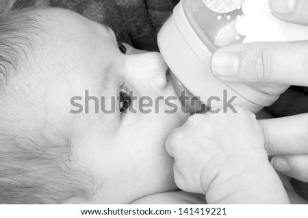 Mother feeding her baby girl with a baby bottle. - stock photo