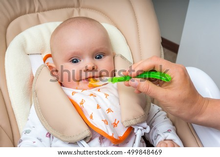 Mother feeding her baby girl with a spoon and baby girl eating one of her first meals