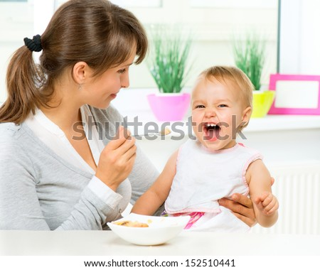 Mother Feeding Her Baby Girl with a Spoon. Mother Giving Food to her adorable Child at Home  - stock photo