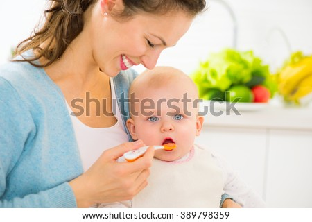 Mother Feeding Her Baby Girl with a Spoon. Mother Giving Food to her adorable Child at Home. Baby food  - stock photo