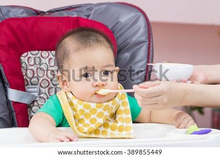 Mother feeding her child - stock photo