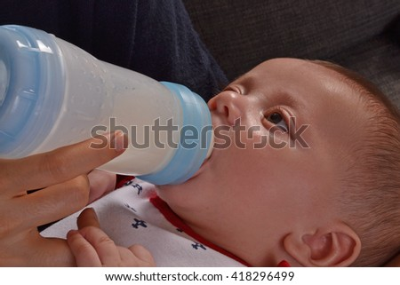 Mother feeding her close up baby boy with a plastic baby bottle. - stock photo