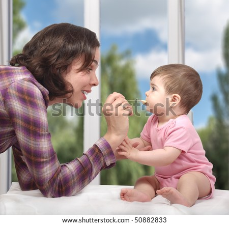 Mother feeding her cute little baby - stock photo