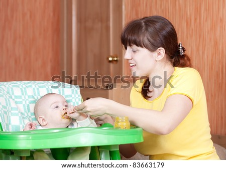 Mother feeding her 6 month old daughter with spoon - stock photo