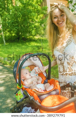 mother feeding her naked baby son with milk from plastic bottle in stroller outdoor at summer park. Empty space for inscription - stock photo