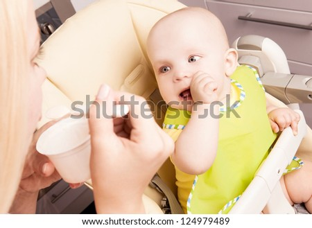 mother feeding her one year old daughter at home - stock photo