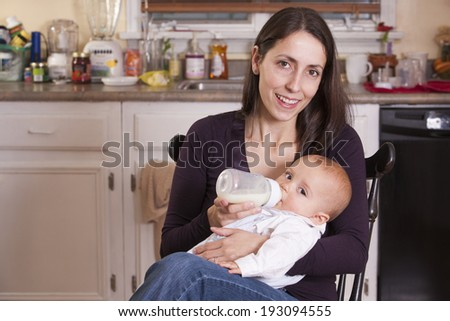 Mother feeding her son from bottle  - stock photo