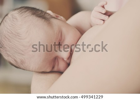 mother feeding her sweet newborn with breast