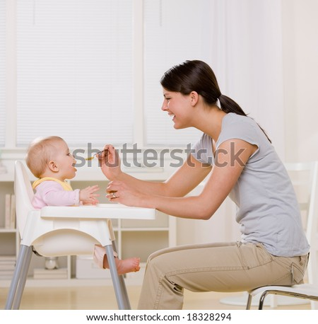 Mother feeding hungry baby in highchair in kitchen - stock photo
