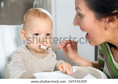 Mother feeding hungry baby in the highchair indoors - stock photo