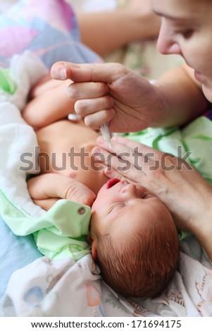 Mother feeding newborn baby milk with syringe  - stock photo