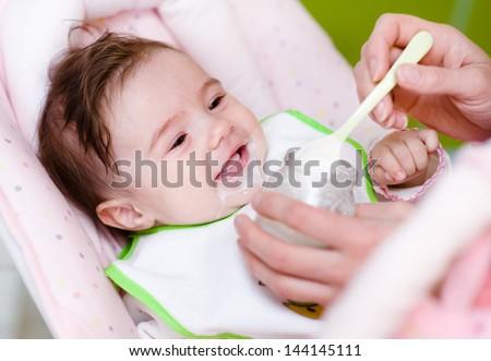 Mother feeding newborn daughter with feeding bottle - stock photo