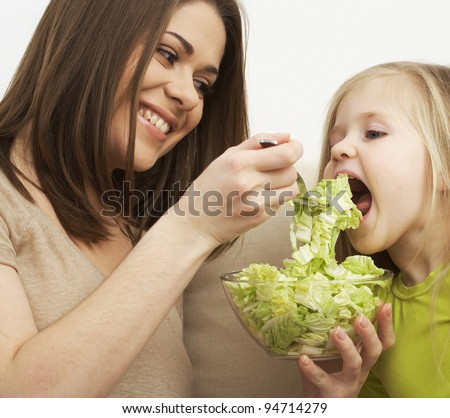 Mother feeds little girl with organic green food - stock photo