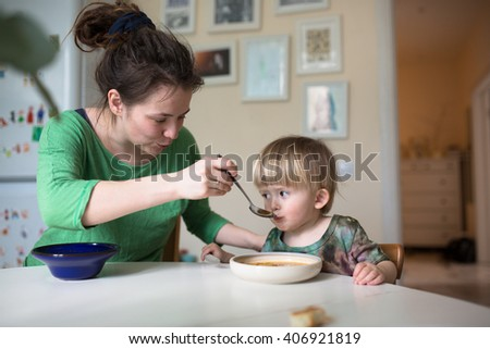 mother feeds the child soup in the bright kitchen at home,  real interior, Mom with dreadlocks, casual - stock photo