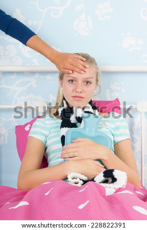 Mother feeling at head of sick teen girl laying in bed  - stock photo