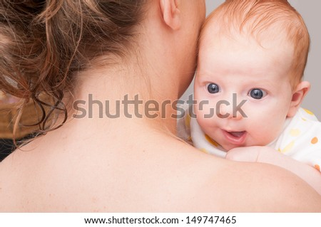 Mother from Behind Holding  Happy Newborn Baby - stock photo