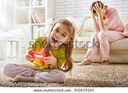 mother frustrating that her child playing video games - stock photo