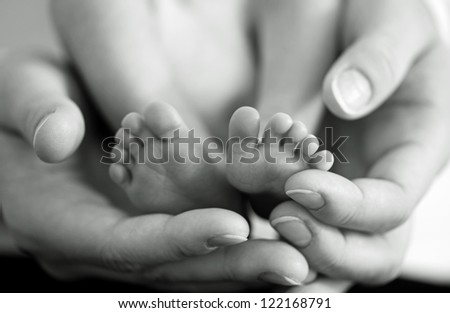 Mother gently hold baby leg in hand. Black and white image with soft focus on babie's foot