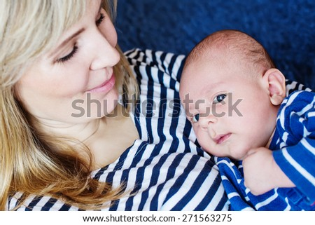 Mother gently holding a newborn baby on a blue background - stock photo