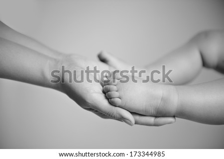 Mother gently holding baby feet, black and white photography - stock photo