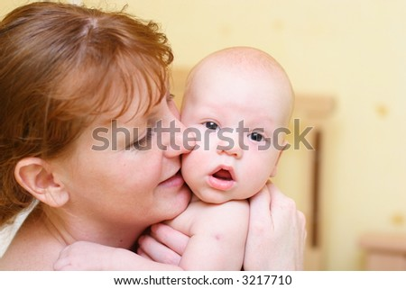 Mother gently holding baby in hands and smile. Close-up view.