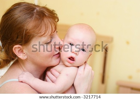Mother gently holding baby in hands. Baby surprised.