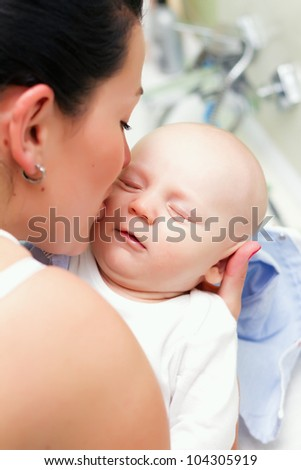 Mother gently kissing her baby