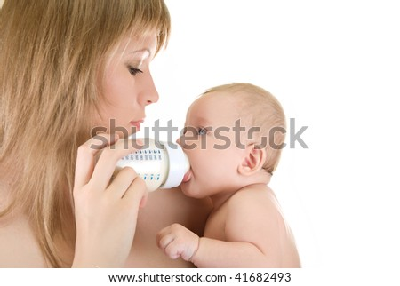 Mother give drink her baby boy by feeding bottle over white - stock photo