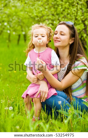 Mother gives her curly daughter a dandelion to blow it  away - stock photo