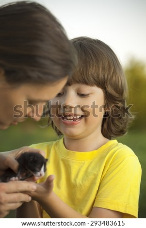 Mother gives her son a small kitten - stock photo